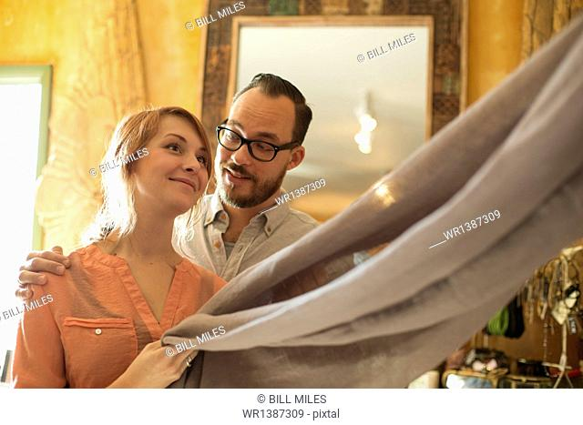 Two people, a couple running an antique store. Small business. Holding a piece of linen fabric