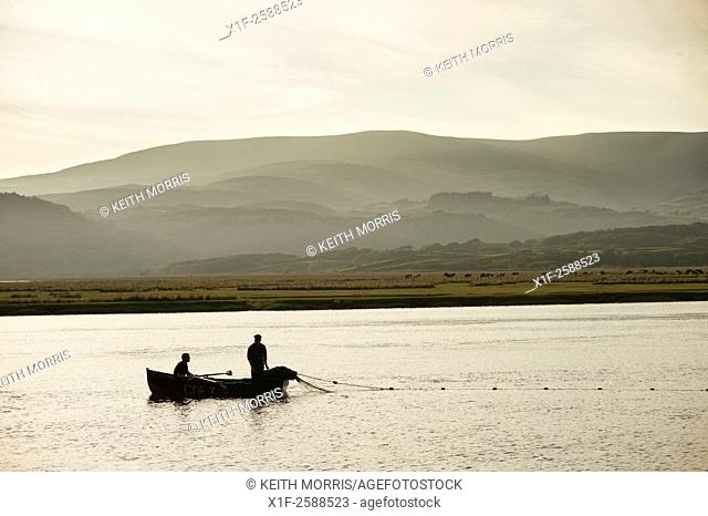 Seine netters on the Dyfi: Licensed fishermen in a small rowing boat using traditional 'seine netting' techniques to fish for sewin and salmon at dusk and high...