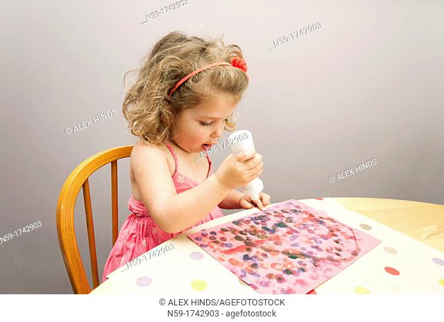 Three year old girl painting a dot picture