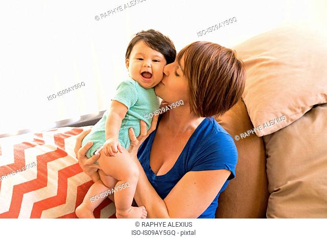 Mother sitting on sofa kissing baby's cheek