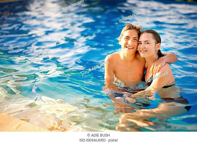 Portrait of teenage boy and girl in outdoor swimming pool