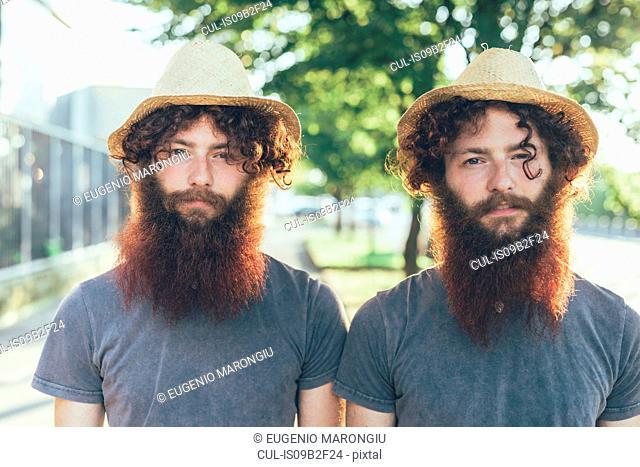 Portrait of identical male hipster twins wearing straw hats on sidewalk