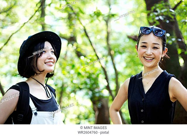 Two smiling young women standing in a forest