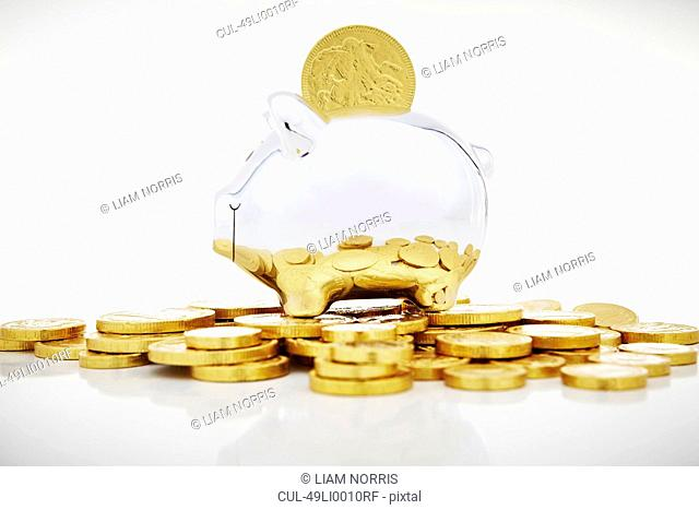 Stack of gold coins by piggy bank