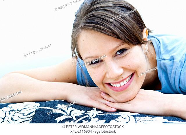 Young woman lying on a couch, laughing (model-released)
