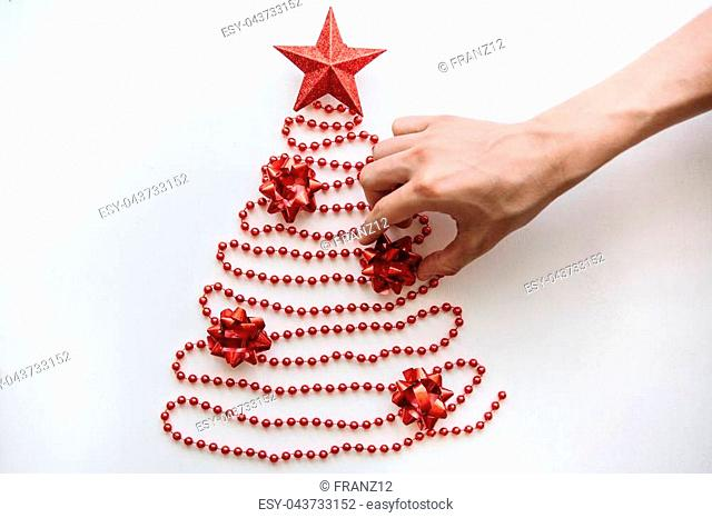 A person makes a creative Christmas or New Year tree made of beads in a minimalistic style and decorates with a star. Celebratory concept or creative idea or...