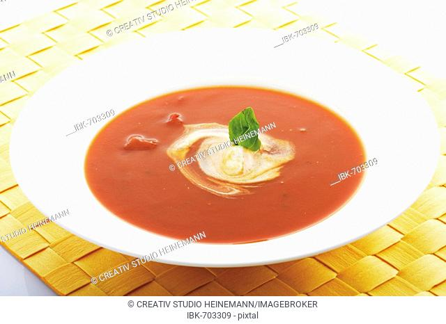 Tomato soup topped with a dollop of cream and basil