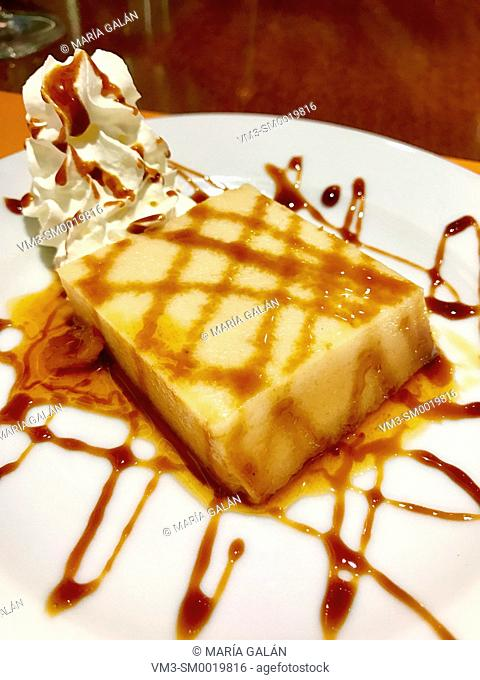 Pudding with cream and toffee syrup. Close view