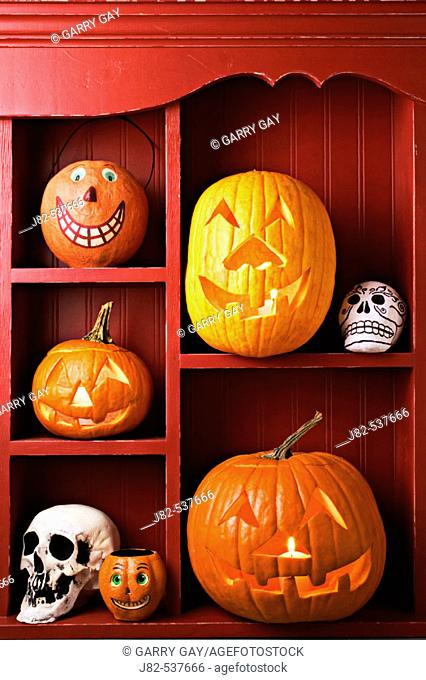 An old red cabinet with Halloween items, carved pumpkins, skulls