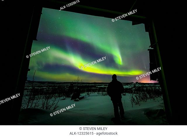 A silhouetted man observes the aurora borealis, framed by the entrance of a decaying building, Interior Alaska, USA