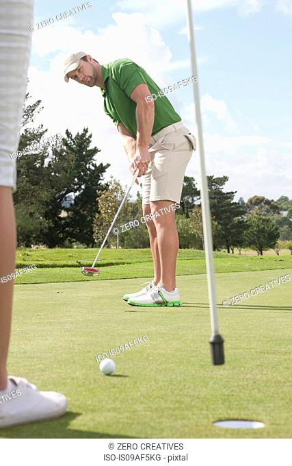 Young male golfer putting on golf green