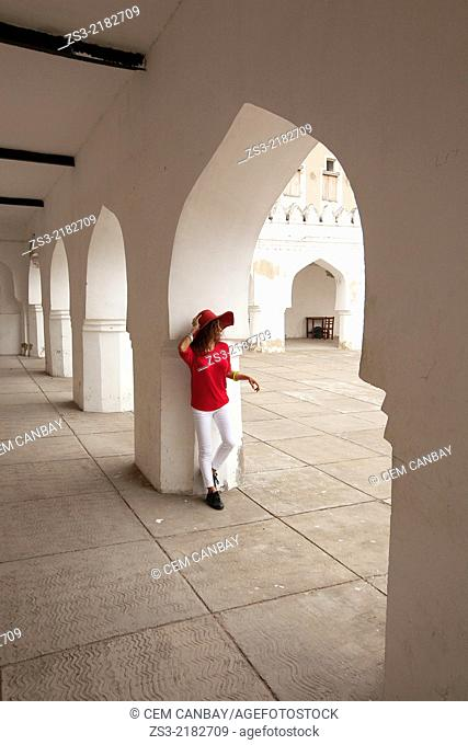 Woman with red hat posing inside the Forodhani Primary School, Stone Town, Unguja Island, Zanzibar Archipelago, Tanzania, East Africa
