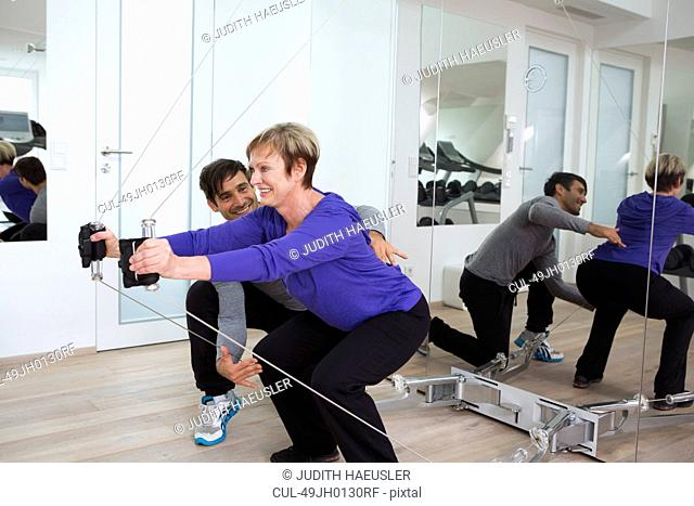 Trainer adjusting woman's form in gym