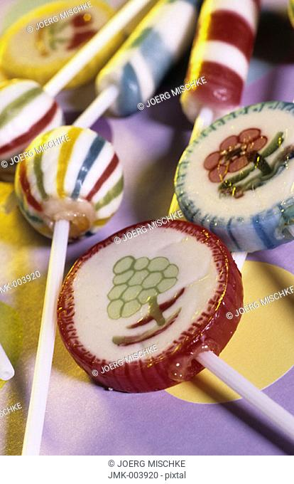 Different kinds of lollipops lying on a coloured ground