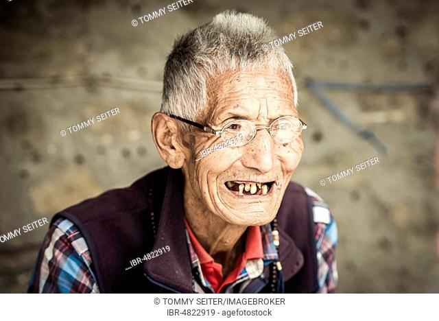 Man with few teeth, exile Tibetan, Pokhara, Kathmandu Valley, Nepal