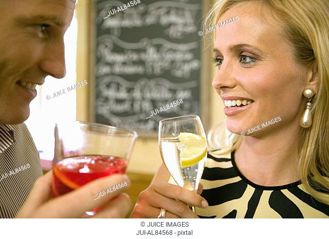 Couple toasting with cocktails in restaurant