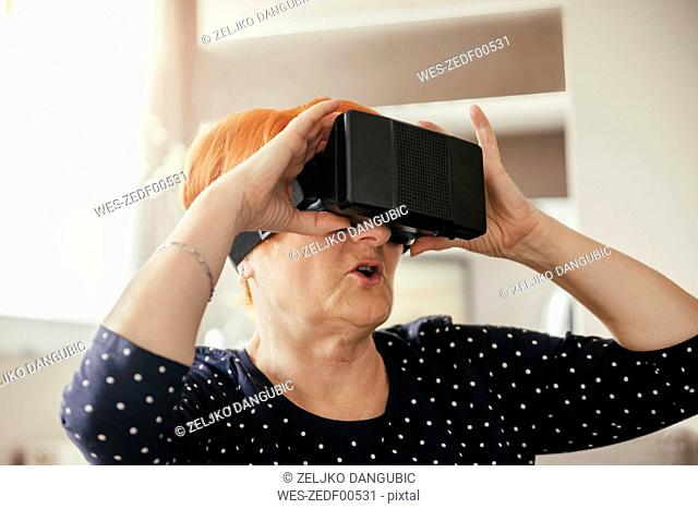 Senior woman at home wearing VR glasses