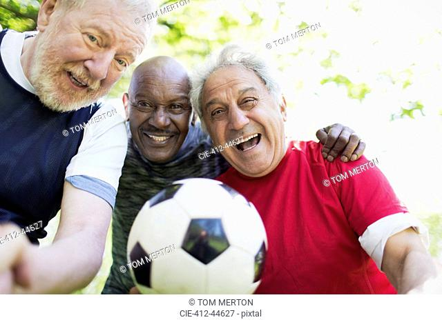 Portrait active senior men friends playing soccer