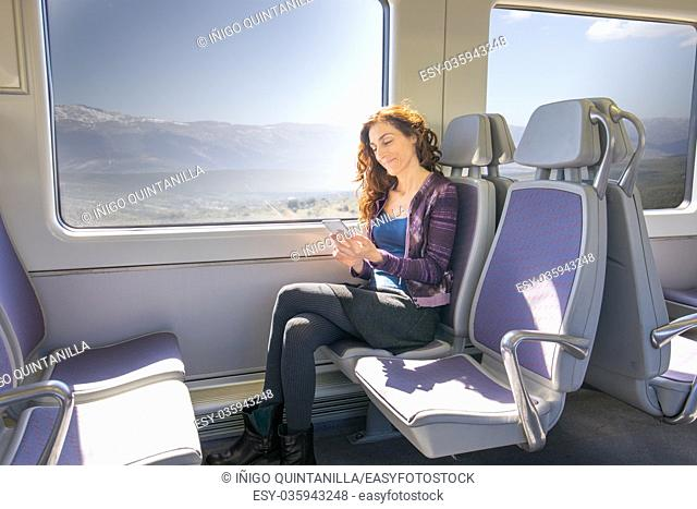 red hair smiling woman dressed in purple and blue, traveling by train sitting, using , surfing internet, reading or typing on mobile smart phone