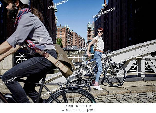 Germany, Hamburg, woman with electric bicycle watching man passing by on bicycle