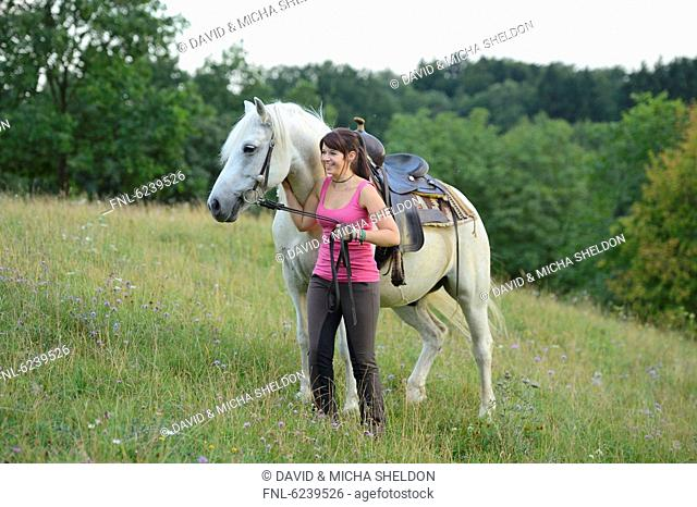 Smiling teenage girl with horse on meadow