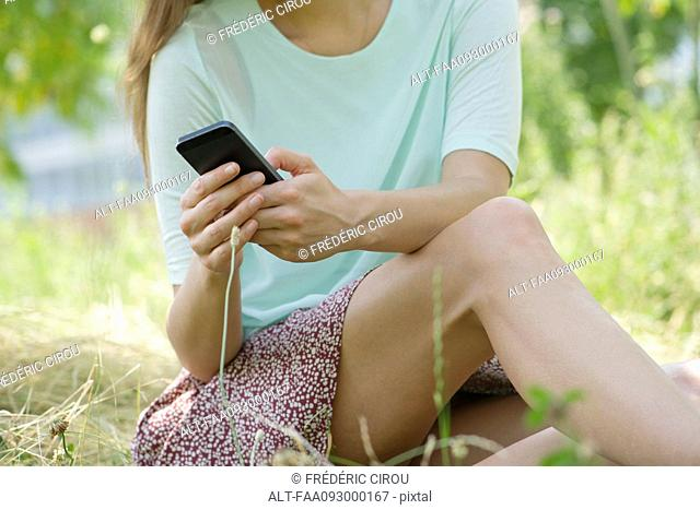 Woman relaxing outdoors with smartphone