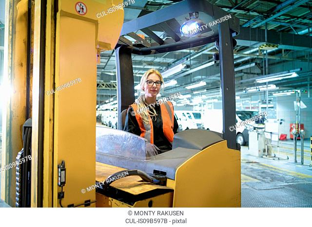 Portrait of female forklift driver in car factory