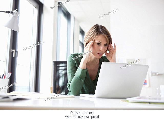 Concentrated businesswoman working on laptop at office desk