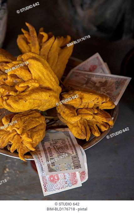 Close up of fruit and money in shrine