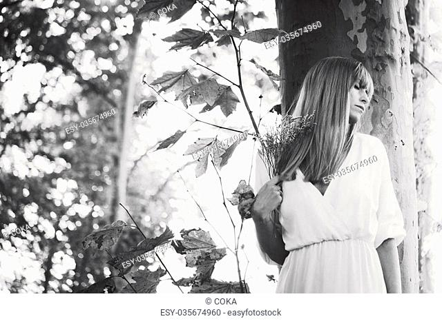 young woman in white dress stand by tree hold twig of flower in hand, eyes closed, black and white, small amount of grain added