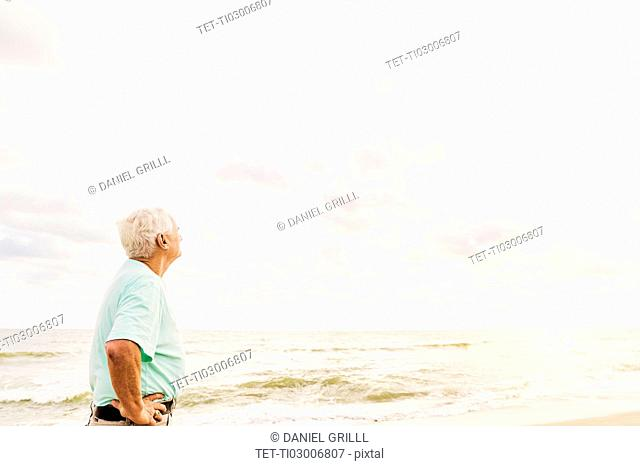 Side view of senior man standing on beach