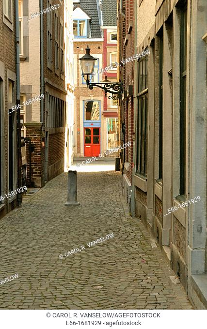 small cobblestoned side street in the Wijck neighbourhood of Maastricht with old fashioned streetlamp on building