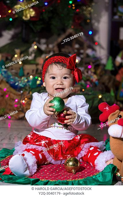 Baby girl celebrating Christmas near a tree decorated with lights and Christmas decorations