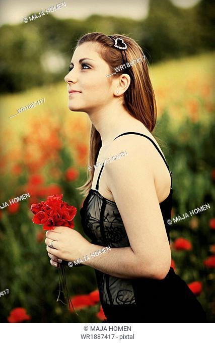 Young woman in a poppy field, Croatia, Europe
