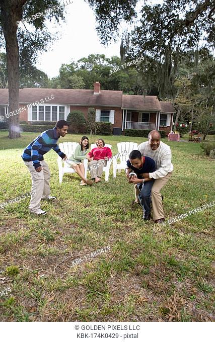 Family playing football in backyard