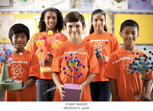 A group of girls and boys wearing the teeshirt of the Science Club, making molecular structure models