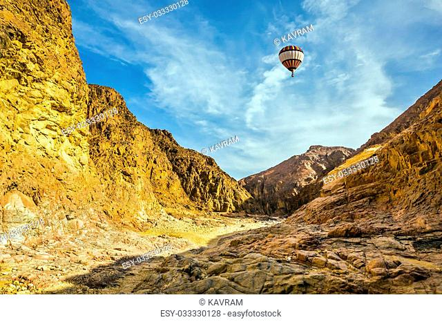 Walking route on picturesque Black canyon in Israel. The multi-colored balloon over the hot desert