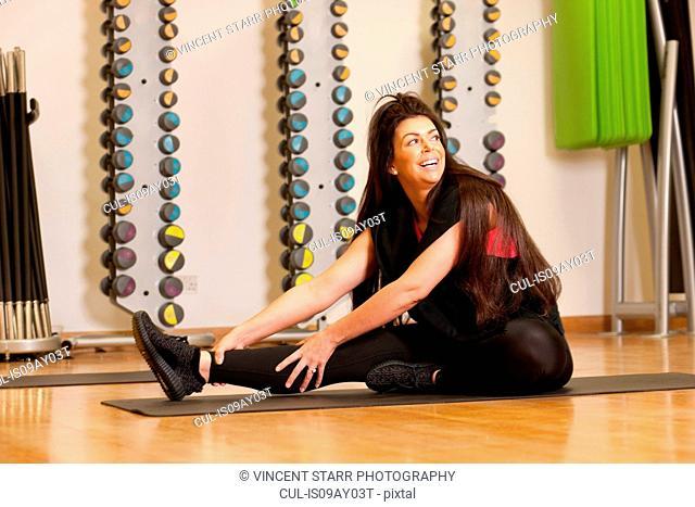 Woman in gym sitting on yoga mat stretching legs