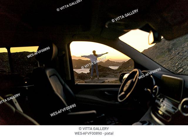 Young woman enjoying sunset at the beach, view through car