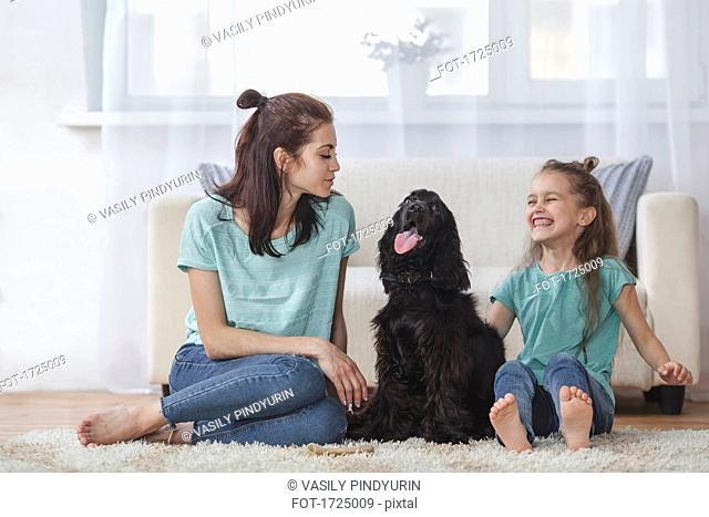 Cheerful girl sitting by Cocker Spaniel and mother in living room at home