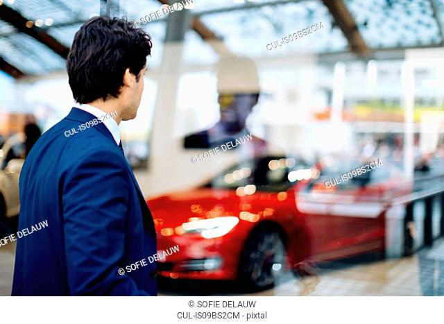 Businessman looking through glass wall at sports car in showroom