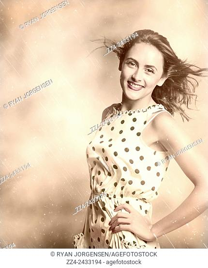 Olden day picture with worn scratches and scuff marks of a very beautiful young brunette lady in elegant polka dot dress smiling with old fashion hair style