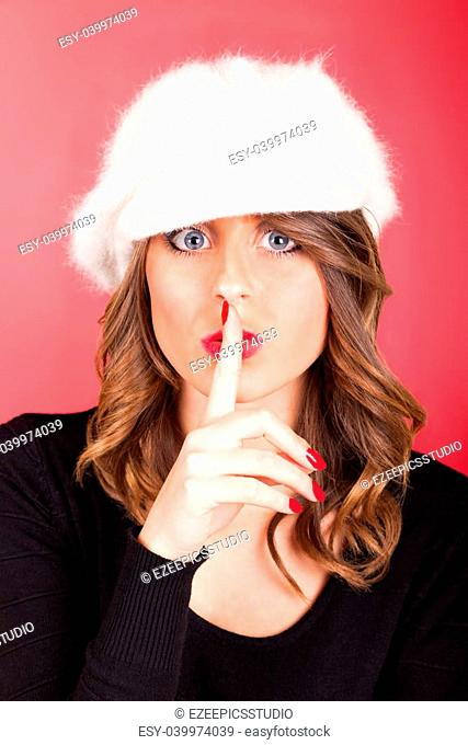 Woman with finger near lips asking the silence