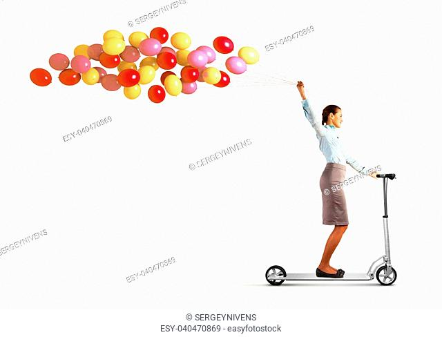 Image of young woman riding scooter with bunch of balloons in hand