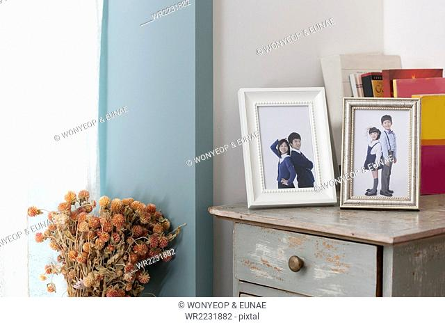 Children's photos in frames placed on a drawer