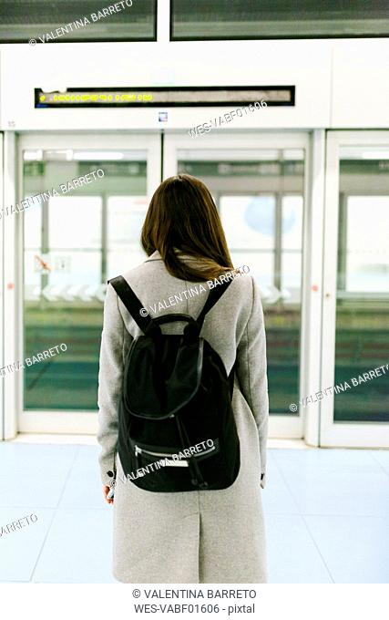 Back view of woman with black backpack