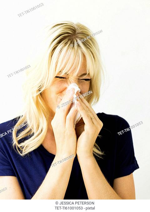 Studio portrait of blonde woman blowing nose