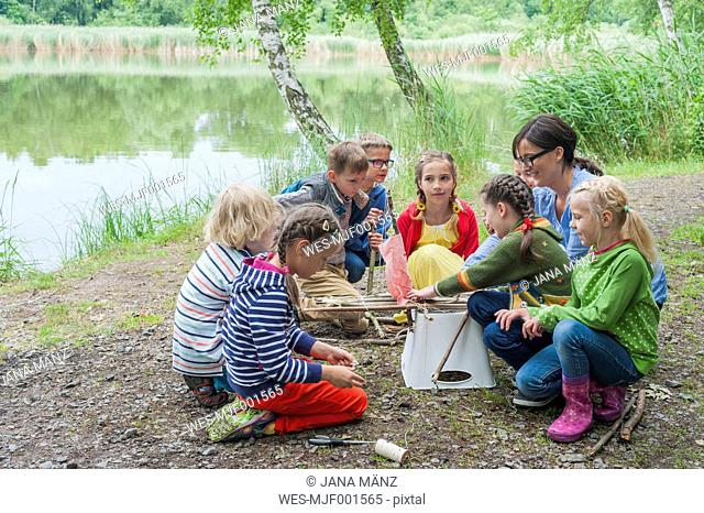 Germany, Children learning how to build a wooden raft