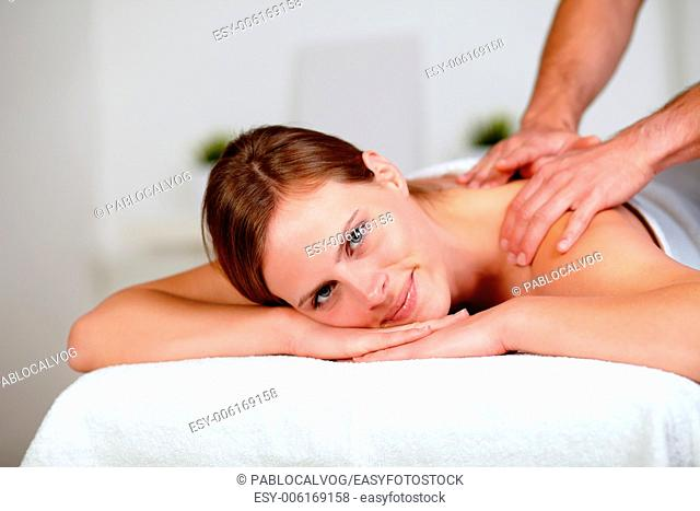 Portrait of a young blonde woman relaxing at a spa while receiving a massage at spa resort