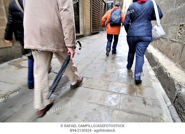 People walking, a man with umbrella, Gothic area, Ciutat Vella, Barcelona, Catalonia, Spain